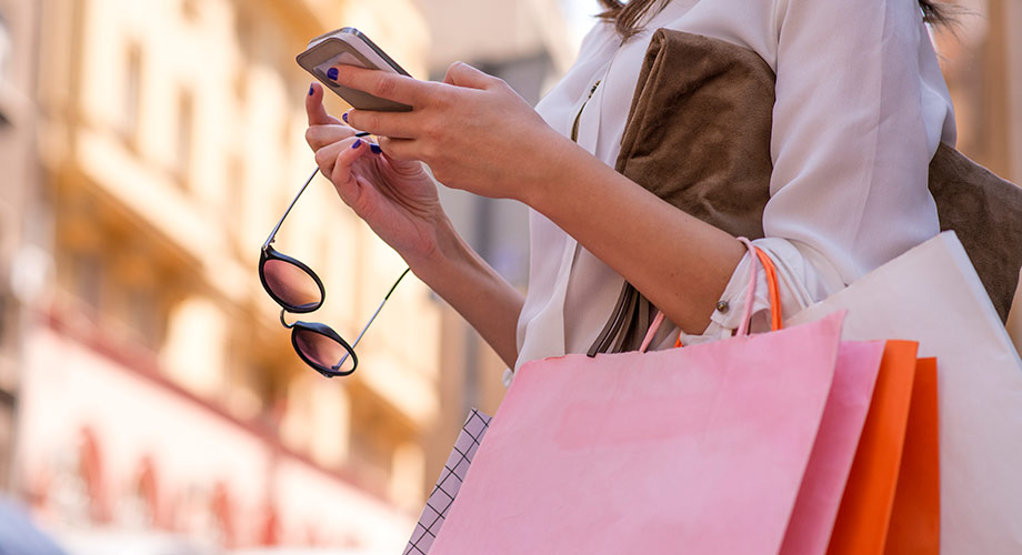 Woman holding smartphone and shopping bags