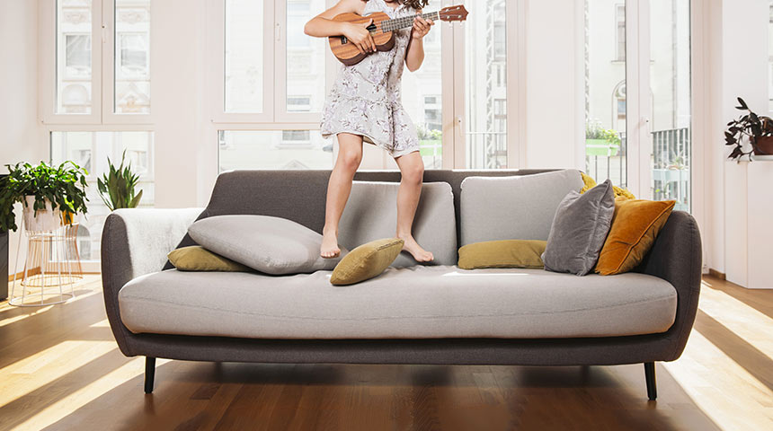 Little girl jumping on a sofa