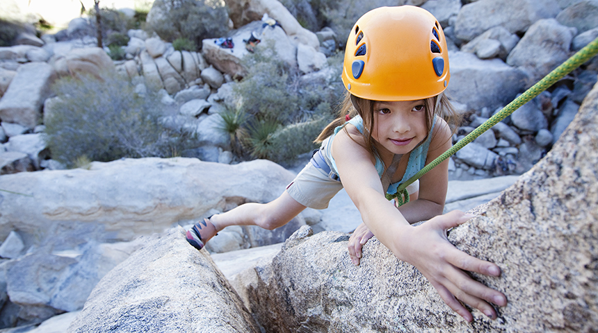 Little girl climbing onto climbing wall with helmet
